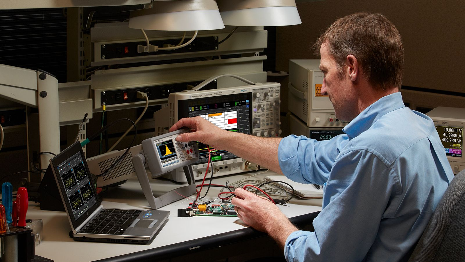 Engineer troubleshooting electronic boards with Keysight's digital multimeter in the lab