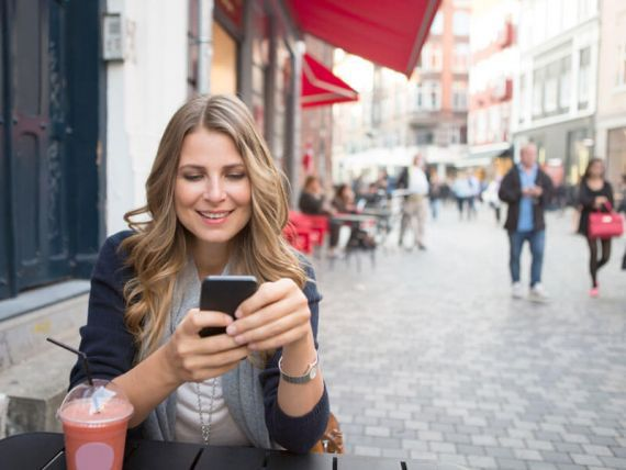 A woman sitting outside looking at her cellphone
