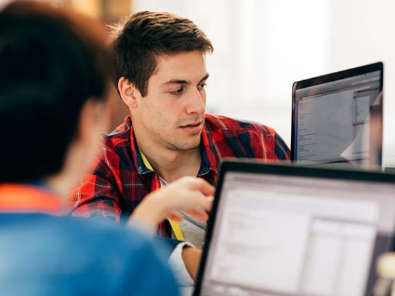 people coding at computer screen